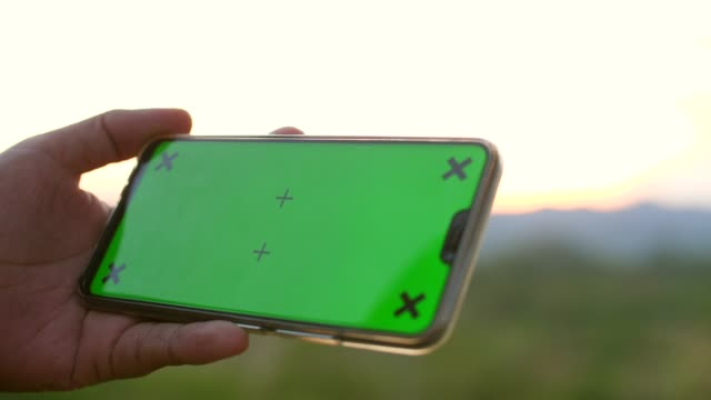 close-up of man holding smart phone with green screen in nature with landscaped mode, chroma key - outdoors stock videos & royalty-free footage