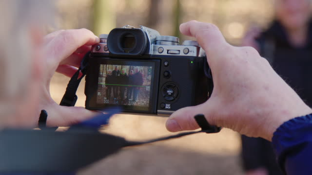 nahaufnahme des mannes fotografiert freunde im wald - photographing stock-videos und b-roll-filmmaterial