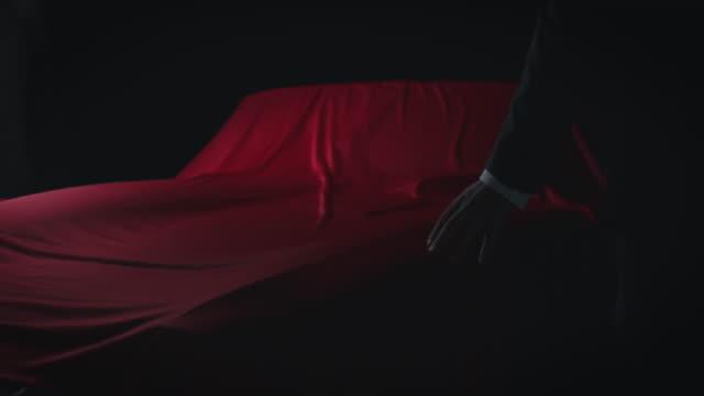 vídeos y material grabado en eventos de stock de close-up de hombre eliminando el satén rojo del coche - cubrir