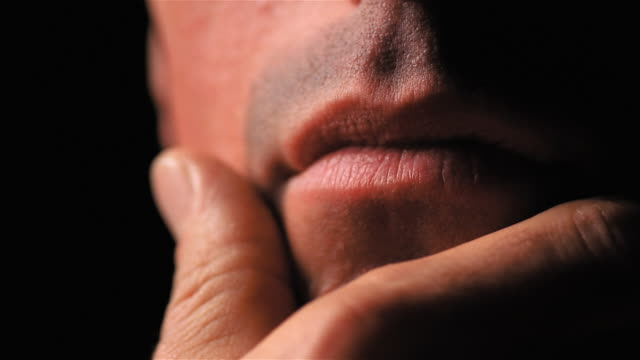 closeup of man rubbing hand on his chin - strofinare toccare video stock e b–roll