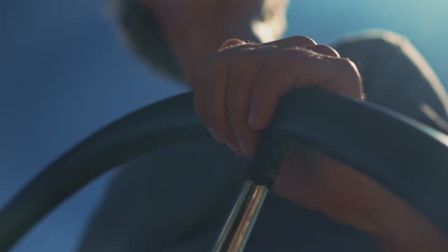 close-up of man steering in yacht on sunny day - steering wheel stock videos & royalty-free footage