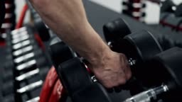 Close-up of man takes dumbbell in gym. Closeup of dumbbells row