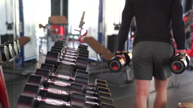close-up of man takes dumbbell in gym. closeup of dumbbells row - human limb stock videos & royalty-free footage