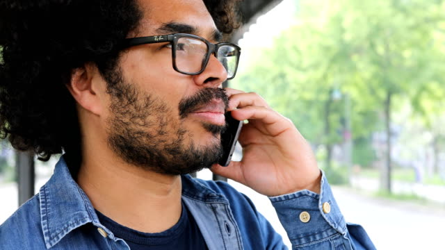 Close-up of man talking on mobile phone in city