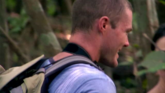 close-up of man turning and smiling at camera during hike with woman in forest - paar mittleren alters stock-videos und b-roll-filmmaterial