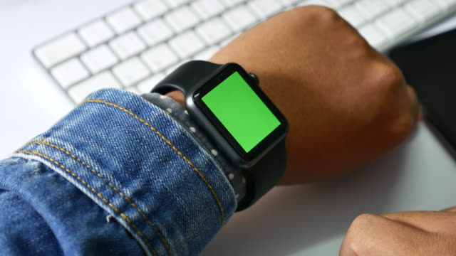 vídeos de stock e filmes b-roll de close-up of man using smart watch with green screen, chroma key - plus key