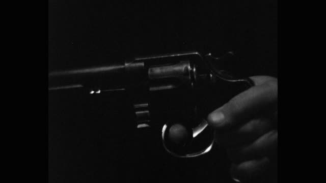 close-up of man's finger pulling the trigger of a gun at night - pulling stock videos & royalty-free footage
