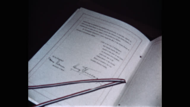 close-up of man's hand closing the north atlantic treaty, with signature of us president harry truman, white house, washington dc, usa - part of stock videos & royalty-free footage