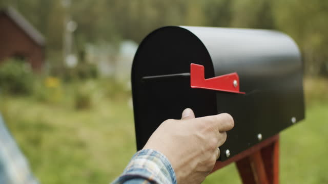 close-up of man's hand putting letter with voting ballot into a mailbox near his house - mail stock videos & royalty-free footage