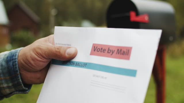 close-up of man's hand putting letter with voting ballot into a mailbox near his house - citizenship stock videos & royalty-free footage