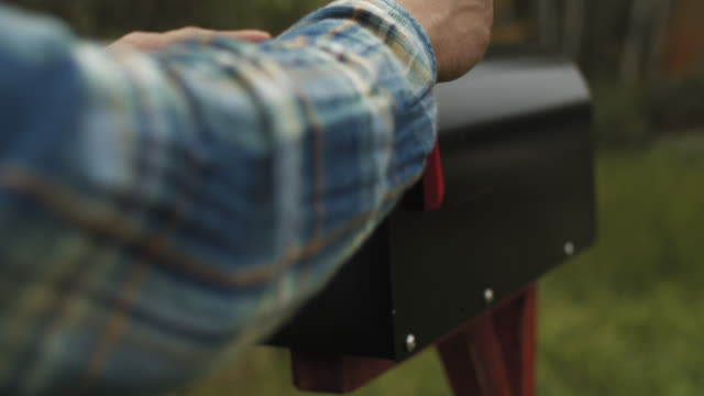 close-up of man's hand putting letter with voting ballot into a mailbox near his house - scheda di votazione video stock e b–roll