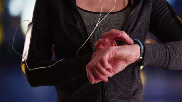 stockvideo's en b-roll-footage met close-up of mature woman jogger using smartwatch - jogster