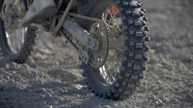 stockvideo's en b-roll-footage met close-up of men riding motocross motorcycles on a dirt off road, accelerating spinout with dirt flying. - men