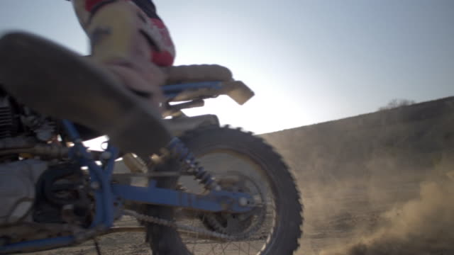 close-up of men riding motocross motorcycles on a dirt off road, accelerating spinout with dirt flying. - slow motion - motocross stock videos & royalty-free footage