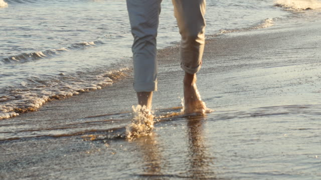 Close-up of men's foot on the sand at sunset
