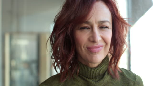 close-up of middle-aged woman with red hair turning toward camera and smiling. - 40 44 anni video stock e b–roll