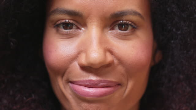 close-up of mixed race, middle-age woman opening and closing eyes while looking at camera. - persona attraente video stock e b–roll