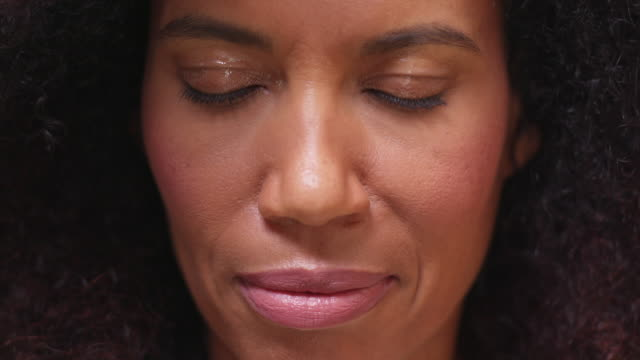 Close-up of mixed race, middle-age woman opening and closing eyes while smiling at camera.