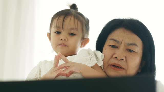 close-up of modern life of thai mother and her daughter are watching cartoon on computer laptop at their bedroom for leisure activity -relative of mother and her baby with mother's day concept - thai ethnicity stock videos & royalty-free footage