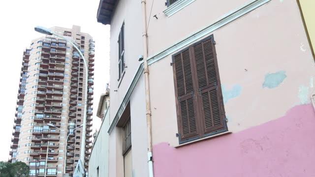 vídeos y material grabado en eventos de stock de close-up of monaco older style building with closed shutters and modern high rise apartment building behind - detalle arquitectónico exterior