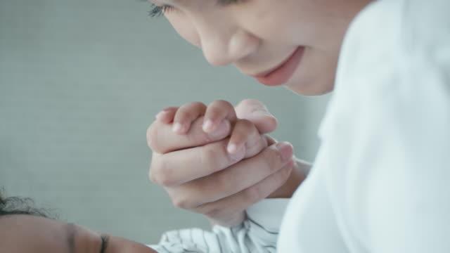 vídeos de stock, filmes e b-roll de close-up da mãe segurando a mão do bebê, câmera lenta - fofo descrição geral