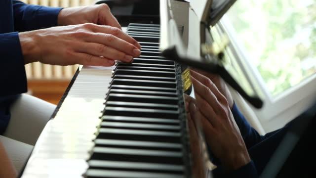vídeos y material grabado en eventos de stock de close-up of mother's hands playing piano while teaching to son - piano