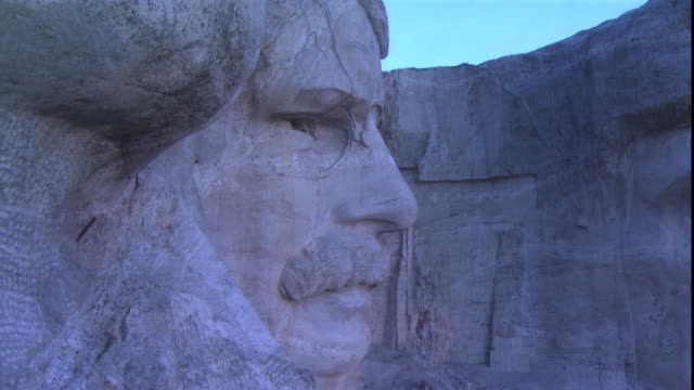 a closeup of mount rushmore focuses on the face president roosevelt and the blue sky. - mt rushmore national monument stock videos & royalty-free footage