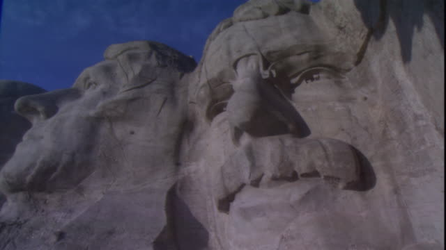 a closeup of mount rushmore focuses on the faces of u.s. presidents roosevelt and jefferson. - 美術工芸品点の映像素材/bロール
