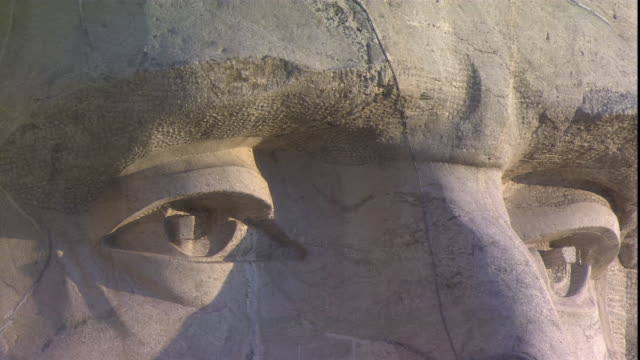 a closeup of mt. rushmore focuses on the face of u.s. president lincoln. - mt rushmore national monument stock videos & royalty-free footage