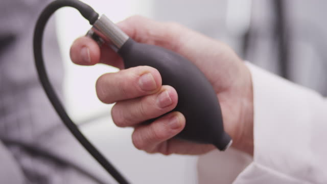 Close-up of nurse's hand pumping blood pressure monitor
