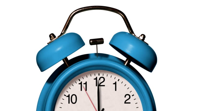 closeup of old fashioned blue alarm clock rings on white background - clock stock videos & royalty-free footage