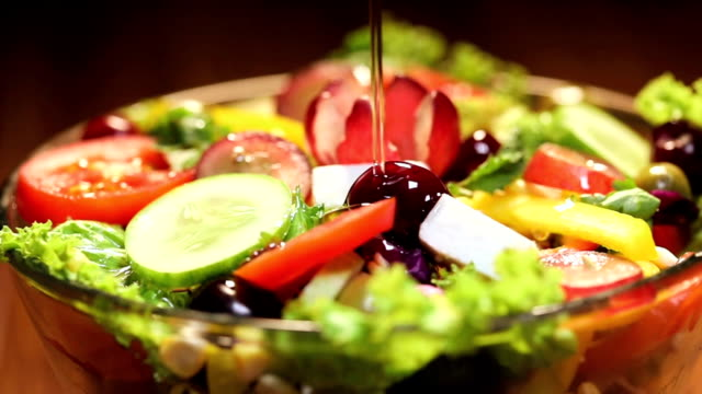 close-up of olive oil pouring into vegetable salad - cucina mediterranea video stock e b–roll