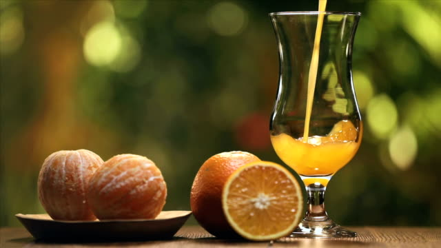 close-up of orange juice pouring into a glass - orange stock videos & royalty-free footage