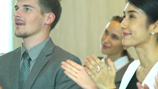 closeup of partners clapping hands after the business seminar. professional education, work meeting, presentation or coaching concept. - etnia video stock e b–roll