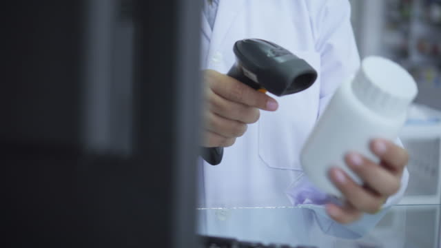 vídeos y material grabado en eventos de stock de close-up del farmacéutico que escanea los medicamentos con lector de código de barras - receta médica medicamento