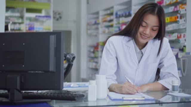 vídeos de stock, filmes e b-roll de close-up do farmacêutico que escreve uma prescrição na mesa, movimento lento - prescription medicine