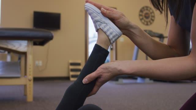 vídeos de stock, filmes e b-roll de close-up do fisioterapeuta esticando a perna de uma jovem garota - physical injury