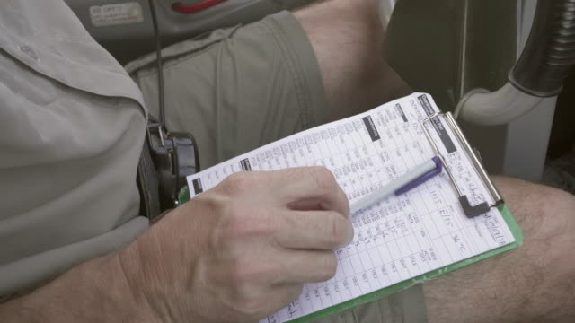 close-up of pilot writing on checklist while flying airplane, midsection of person in air vehicle - sossusvlei, namibia - checklist stock videos & royalty-free footage