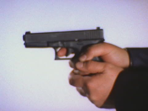 vidéos et rushes de close-up of pistol turning and being aimed - arme à feu