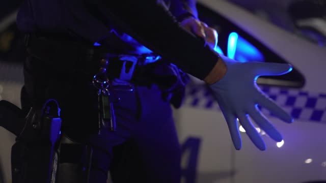 vídeos y material grabado en eventos de stock de close-up of police man hands putting on latex gloves - cuerpo de policía