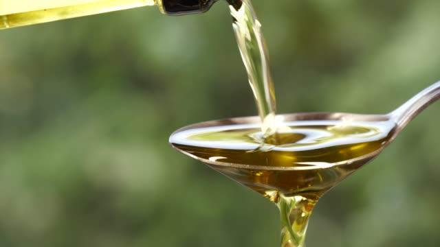 スプーンに油を注ぐクローズアップ - オリーブ油点の映像素材/bロール
