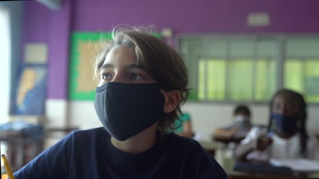 教室での授業中に注意を払う生徒のクローズアップ。コーヴィッド-19 コンセプト - 消しゴム点の映像素材/bロール