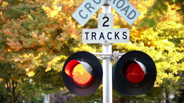 close-up of railroad crossing sign with red lights flashing - level crossing stock videos & royalty-free footage
