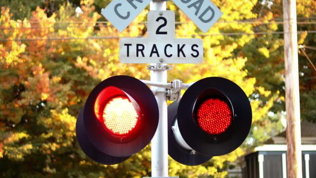 nahaufnahme des bahnübergangsschildes mit roten lichtern blinken - lokomotive stock-videos und b-roll-filmmaterial