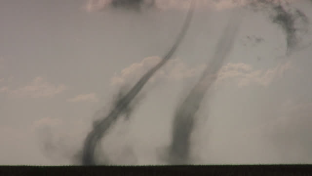 close-up of rare side-by-side landspout tornadoes intersecting and crossing paths over rural field. - alley stock videos & royalty-free footage