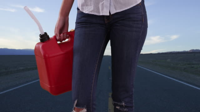 stockvideo's en b-roll-footage met close-up of red gas can held by woman in need of fuel outside on scenic highway - te klein