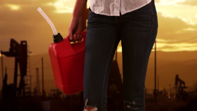 close-up of red gas can held by woman standing outside near some pumpjacks - hold me tight stock videos & royalty-free footage
