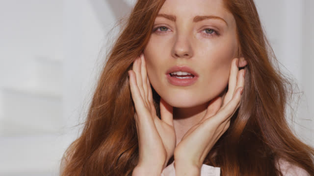 close-up of red head touching her face and neck while hair blows in breeze with a smile - human hair stock videos & royalty-free footage