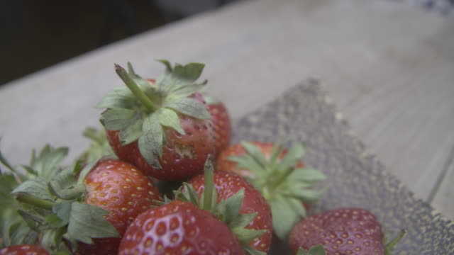 close-up of red ripe strawberries with green sprigs - raw food diet stock videos & royalty-free footage