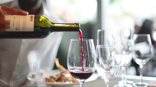 Close-up of red wine being poured into glass in restaurant